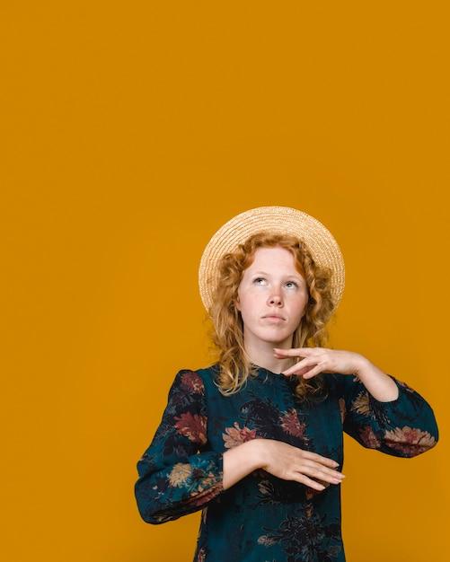 Thoughtful curly redhead woman in studio Free Photo