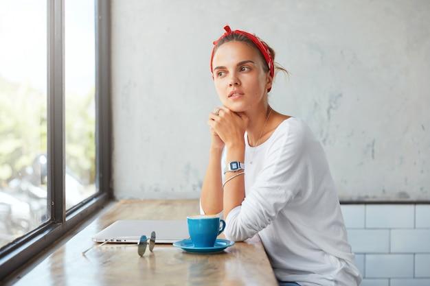 Задумчивая милая женщина-блогер, одетая в повседневную одежду, сидит в кафе, размышляет о чем-то, глядя в окно, пользуется портативным компьютером, пьет горячий напиток, отдыхает после работы Бесплатные Фотографии