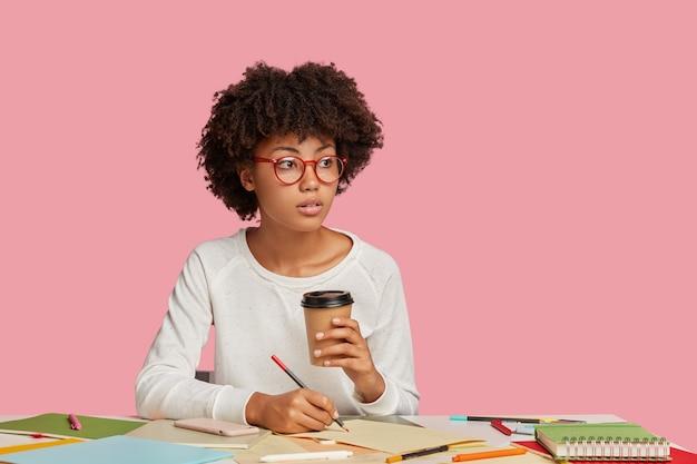 Задумчивая темнокожая девушка в круглых очках делает заметки на чистом листе бумаги, держит кофе на вынос Бесплатные Фотографии