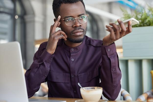 Imprenditore maschio premuroso dalla pelle scura in occhiali, ha una pausa caffè dopo un duro lavoro, fa un rapporto di lavoro sul computer portatile Foto Gratuite