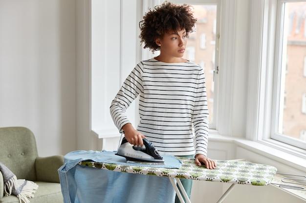 縞模様の服を着た思いやりのある暗い肌の若い主婦はアイロン台に服をアイロンをかけ、電気アイロンスタンドを使用し、窓の外を見る 無料写真