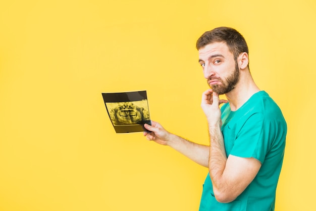 Thoughtful dentist holding teeth x-ray Free Photo