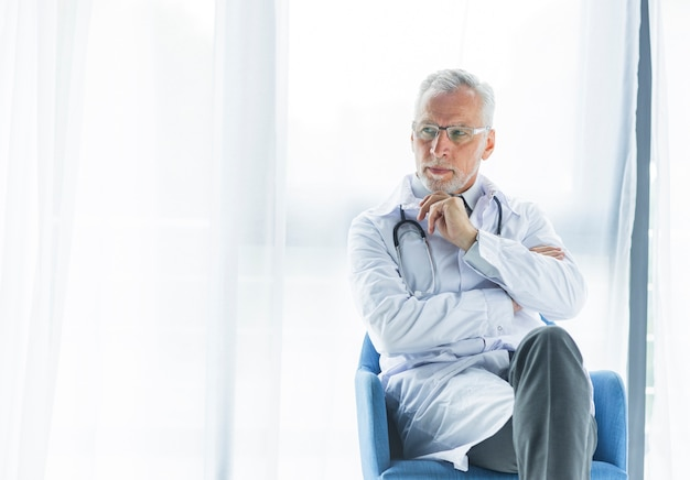 Thoughtful doctor on chair looking away Free Photo