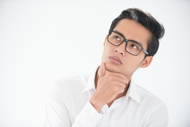 Thoughtful face of young businessman in glasses Free Photo