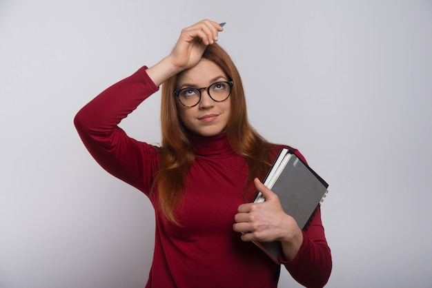 Thoughtful female student with textbooks and pen Free Photo