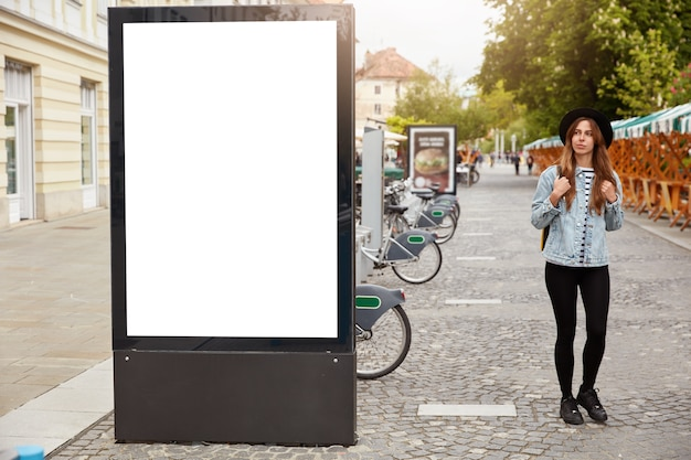 Thoughtful female tourist strolls on footway near lightbox with mock up blank space for your advertising content or commercial information. street style concept. focus on billboard at sidewalk Free Photo