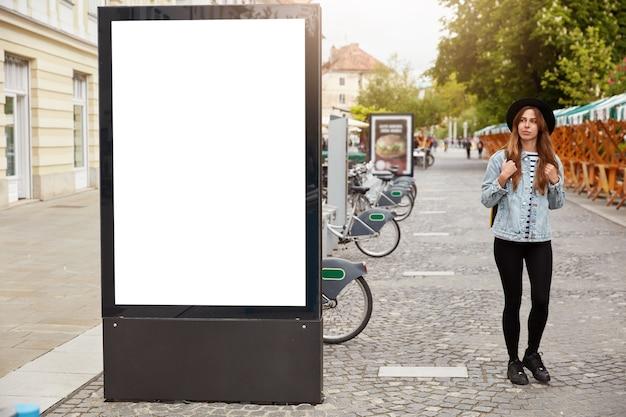 Задумчивая туристка прогуливается по тротуару возле лайтбокса с макетом пустого места для вашей рекламы или коммерческой информации. концепция уличного стиля. сосредоточьтесь на рекламном щите на тротуаре Бесплатные Фотографии