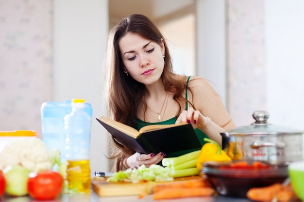 Thoughtful girl cooking with cookbook Free Photo