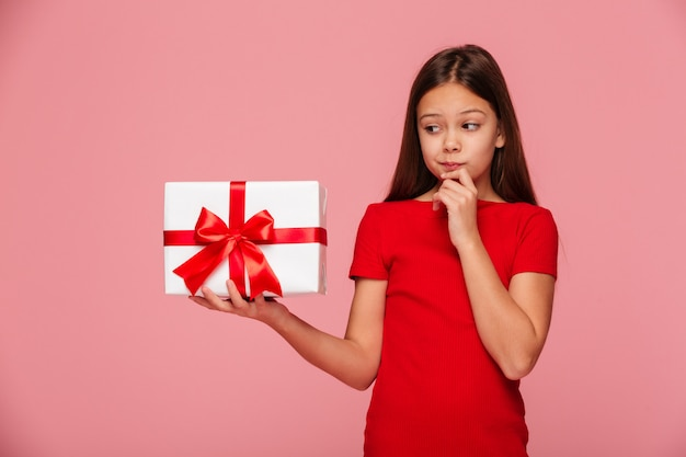 Thoughtful girl looking at gift on hand and thinking about it isolated Free Photo