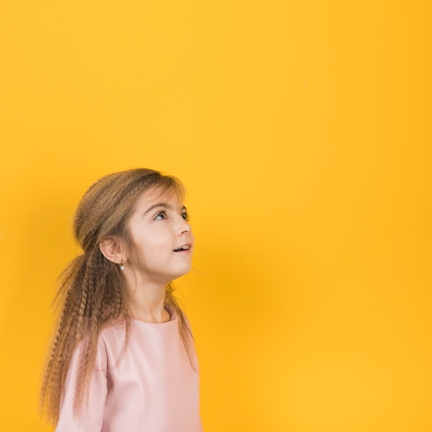 Thoughtful girl looking up on yellow background Free Photo