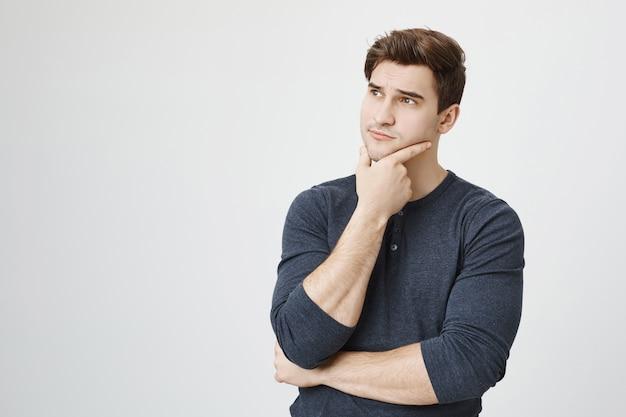 Задумчивый красивый студент-мужчина думает, глядя влево, размышляя Бесплатные Фотографии