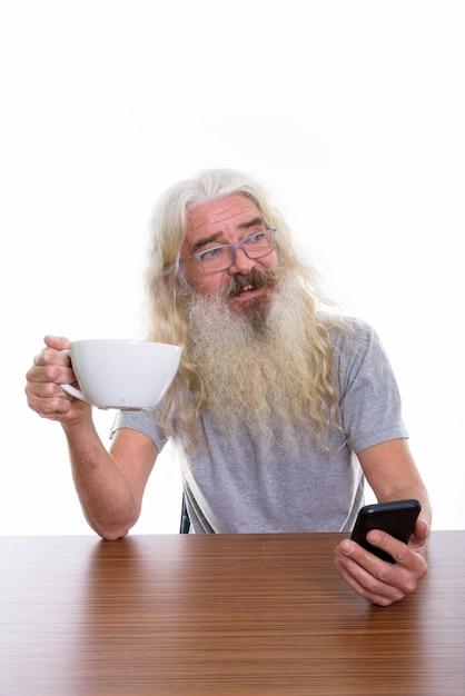 携帯を保持しながら笑顔の思いやりのある幸せなシニアひげを生やした男 Premium写真