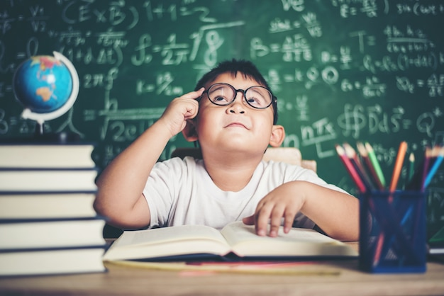 Thoughtful little boy with book in the classroom