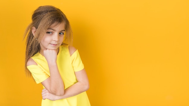 Thoughtful little girl in dress on yellow background Free Photo