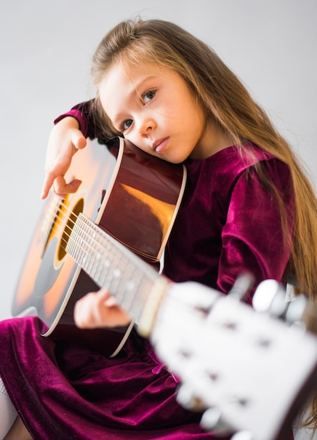 Thoughtful little girl playing acoustic guitar Free Photo