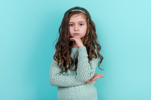 Thoughtful little girl standing on blue background Free Photo