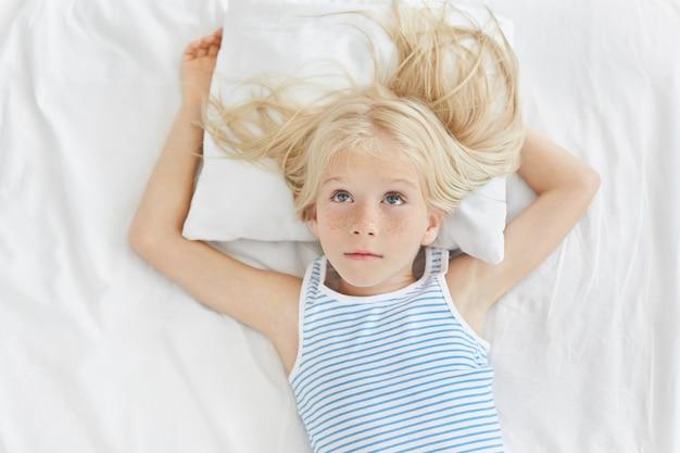 新しい自転車について夢を見て、長いブロンドの髪を見上げて、ストライプのシャツを着て、白い枕の上に横たわって、思いやりのある女の子。子供の部屋の白いベッドで休んで愛らしい少女 無料写真