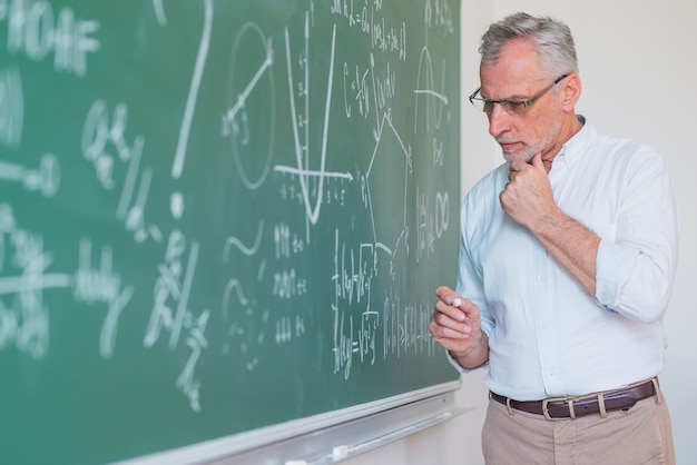 Thoughtful male teacher standing at blackboard and keeping chalk Free Photo