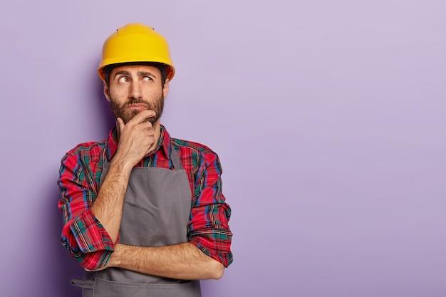 Задумчивый строитель строит человек трогает подбородок Бесплатные Фотографии
