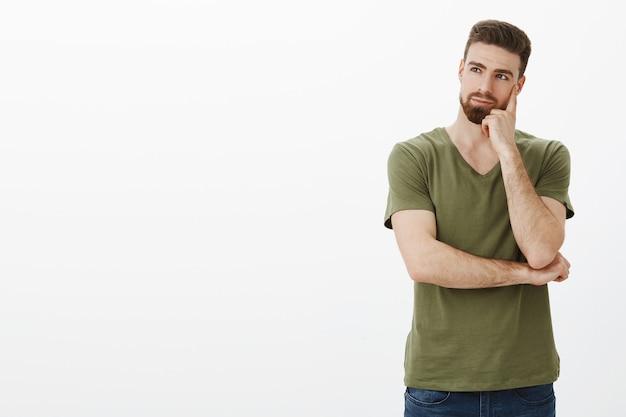 Uomo premuroso che tiene il pugno sulla guancia guardando a sinistra copyspace Foto Gratuite
