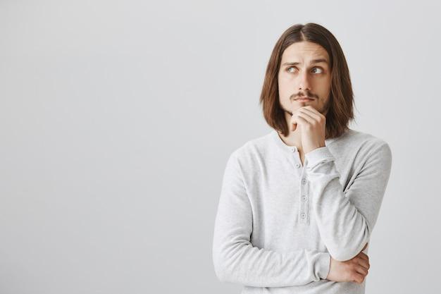 Задумчивый мужчина смотрит влево, думает или делает выбор Бесплатные Фотографии