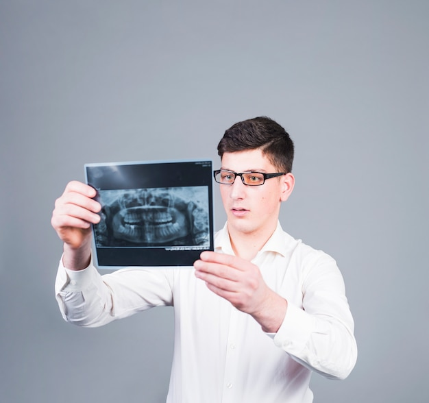 Thoughtful man looking at teeth x-ray Free Photo