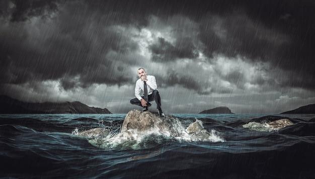 Заботливый человек на скале в бурном море во время шторма. понятие о невзгодах и проблемах на работе. Premium Фотографии