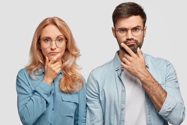 Thoughtful man and woman colleagues hold chins and being concentrated on solving problem, look directly Free Photo