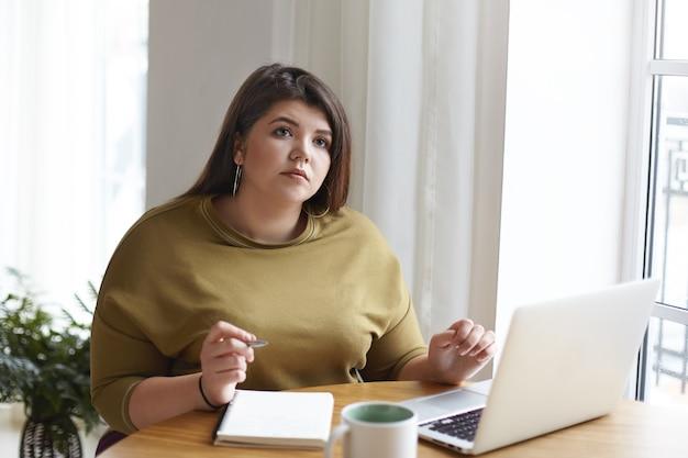 思いやりのある物思いにふける若いぽっちゃり女性ジャーナリストは、ポータブルコンピューター、マグカップを持って机に座って、コピーブックにメモを書きながら見上げ、遠くで働き、オンラインマガジンの新しい記事を書いています 無料写真