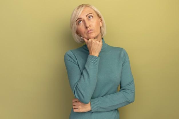 思いやりのあるかなり金髪のスラブ女性はあごを保持し、孤立して見上げる 無料写真