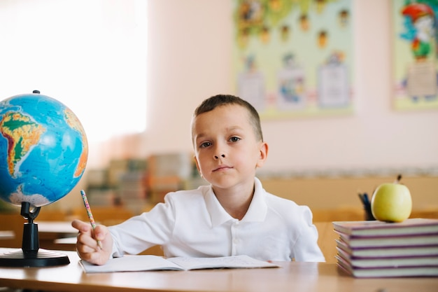 Thoughtful pupil with globe on desk Free Photo