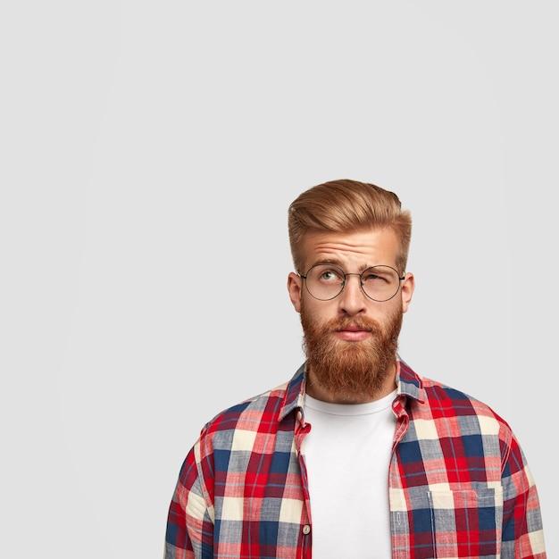 Un uomo premuroso e perplesso ha una folta barba color zenzero che guarda con esitazione verso l'alto, non sa cosa fare dopo la laurea Foto Gratuite