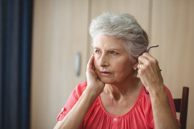 Thoughtful senior woman sitting at a table Premium Photo