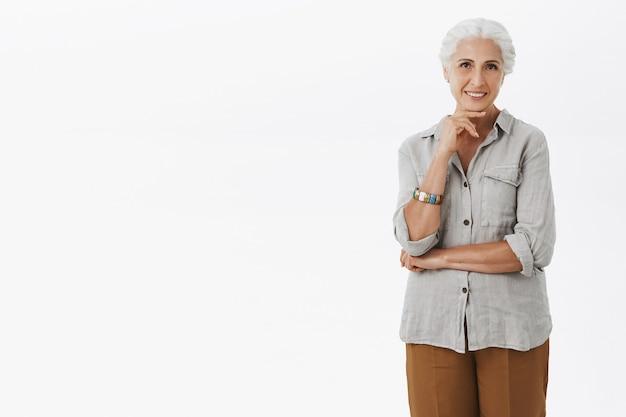 Задумчивая улыбающаяся бабушка смотрит, делая выбор Бесплатные Фотографии