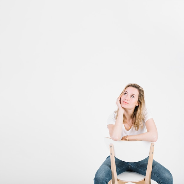 Thoughtful woman on chair Free Photo