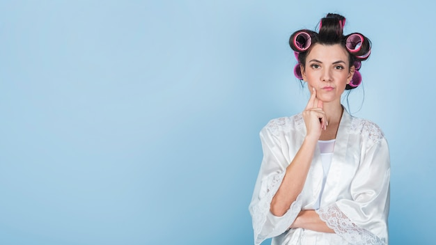 Thoughtful woman in curlers and bathrobe Free Photo