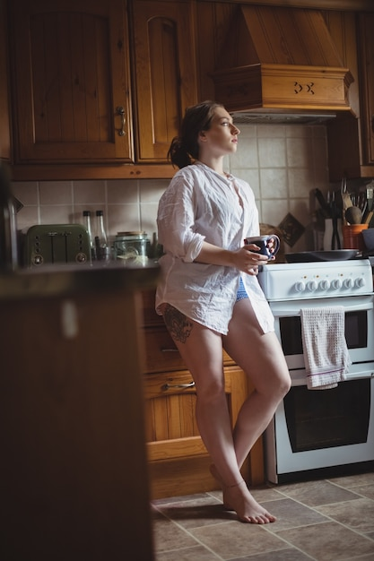Thoughtful woman holding coffee cup in kitchen Free Photo