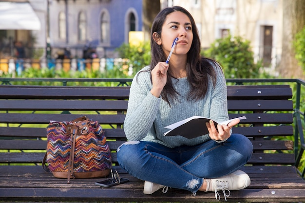Thoughtful woman making notes and sitting on bench outdoors Free Photo