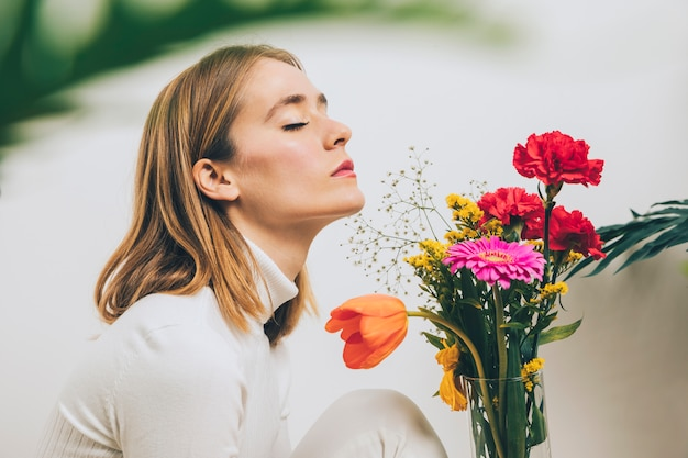 Thoughtful woman sitting with bright flowers in vase Free Photo