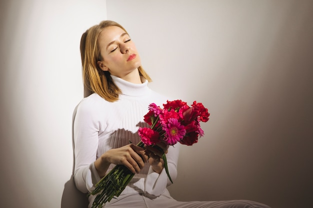 Thoughtful woman sitting with pink flowers bouquet Free Photo