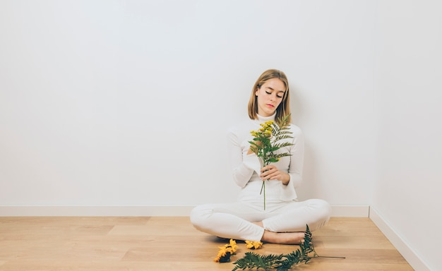Thoughtful woman sitting with plant branches on floor Free Photo