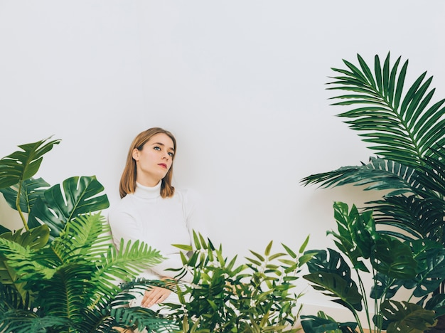 Thoughtful woman standing near green plants Free Photo