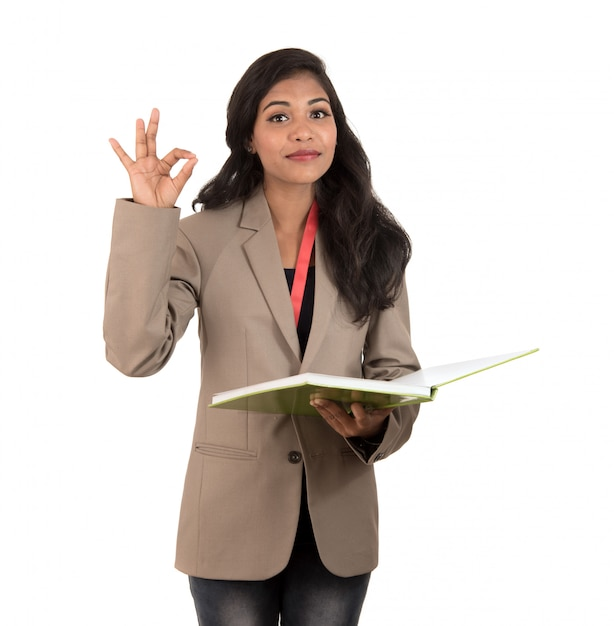 Thoughtful woman student, teacher or business lady holding books and showing ok sign on white space Premium Photo