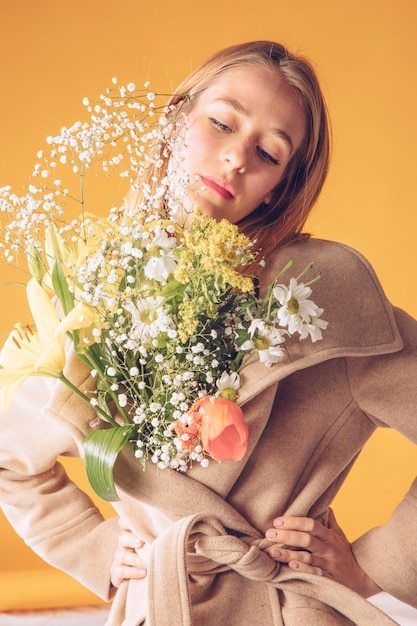 Thoughtful woman with big flowers bouquet in coat Free Photo