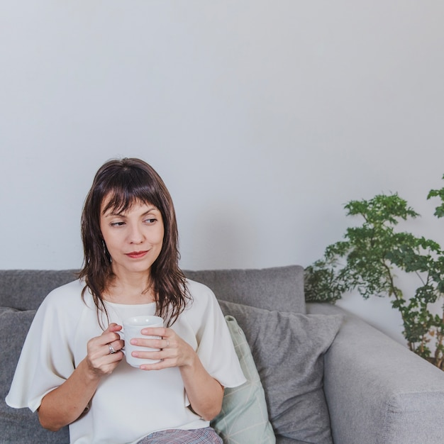 Thoughtful woman with coffee on sofa Free Photo