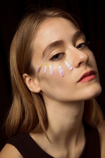 Thoughtful woman with flower petals on face Free Photo