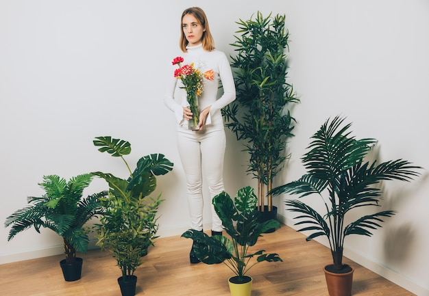 Thoughtful woman with flowers in vase near green plant Free Photo