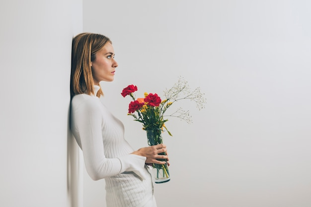 Thoughtful woman with flowers in vase at wall Free Photo