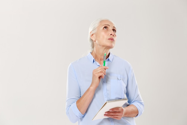 Thoughtful woman with notebook and pen thinking and looking up Free Photo