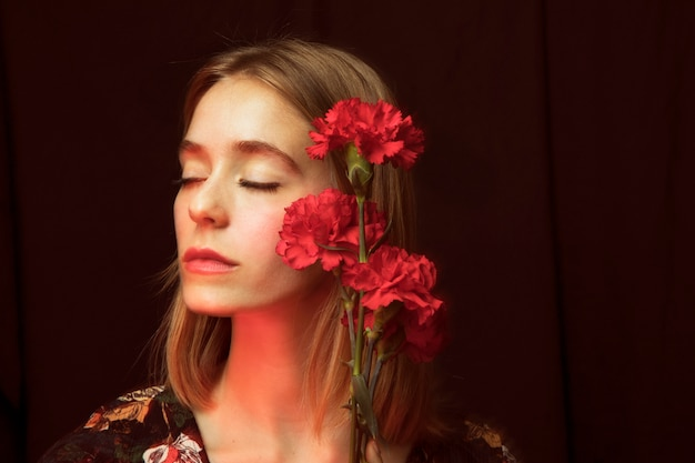 Thoughtful woman with red carnations Free Photo